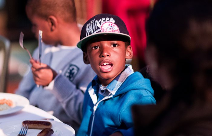 Boy Eating Breakfast at London Charity Event