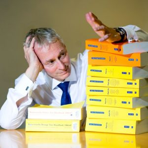 Photograph for PR purposes of accountant with piles of books of legislation