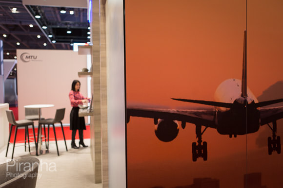Photography of imagery and woman working at Excel exhibition stand