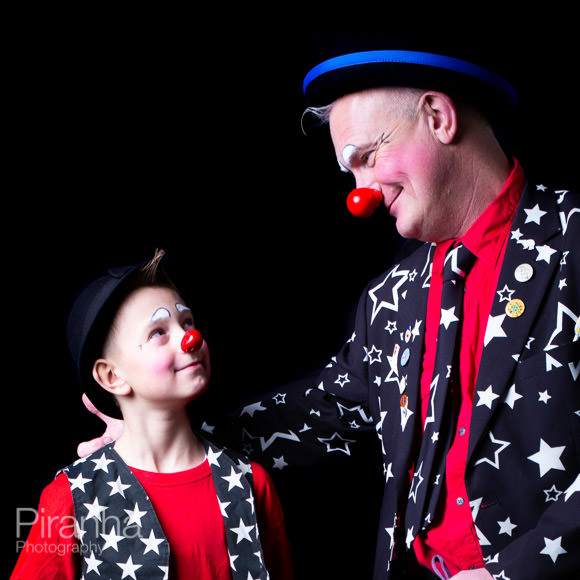Clown father with son posing for photograph