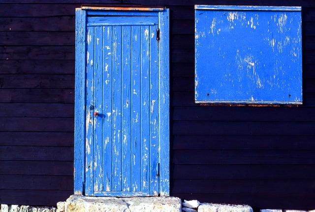 Close up photograph of blue wooden door and window of beah hut